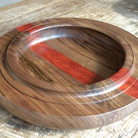 A shallow bowl made of African padauk and American walnut. Finished with shellac and danish oil. Dimensions; total diameter 39,5cm/15.5'' Inside diameter of the rim; 24,5cm/9.5'' Outer bowl rim height ( without pertruding part added ) 6cm/2.3''