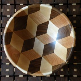 A wooden bowl made of American walnut, cherry, and hard maple. Finished with durable coats of danish oil.