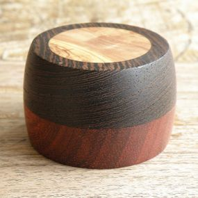 A box made for any type of jewelry or wedding/engagement rings. It is made out of Wenge (top), Padauk (bottom), and the top inlay is Olive wood. The lid has a light but secure fit to the bottom part. The box is finished with a shellac mix. Dimensions, diameter 6.8cm/2.6'' x Height 3.8cm/1.6''