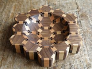 Wood art bowl created by Thomas Anton Geurts. A shallow bowl build up out of 19 hexagons, and joined together using dovetail butterfly's. The hexagons are made of American walnut, and the butterfly's of cherry.