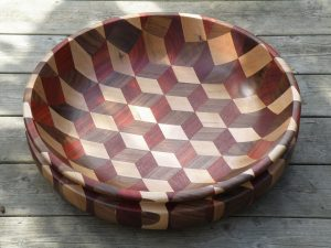 Large woodturned bowl. It is a very colorful piece, thanks to the red Padauk, and different contrasts and streaks in the maple. Made from silver maple, African Padauk and American walnut.