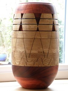 Wood art, wooden art. A vessel made of African Padauk, French oak and African wenge. The top and bottom parts are made of solid blanks of Padauk. The middle sections are segmented, made of double layers of Padauk and Oak. It is finished with a shellac/alcohol/linseed oil mix for the large surfaces, and danish oil for all the notches and interior. Dimensions are HxW 45cm/17.7'' x 25cm/9.8''. Weight is 6.4kg or 14 pounds.